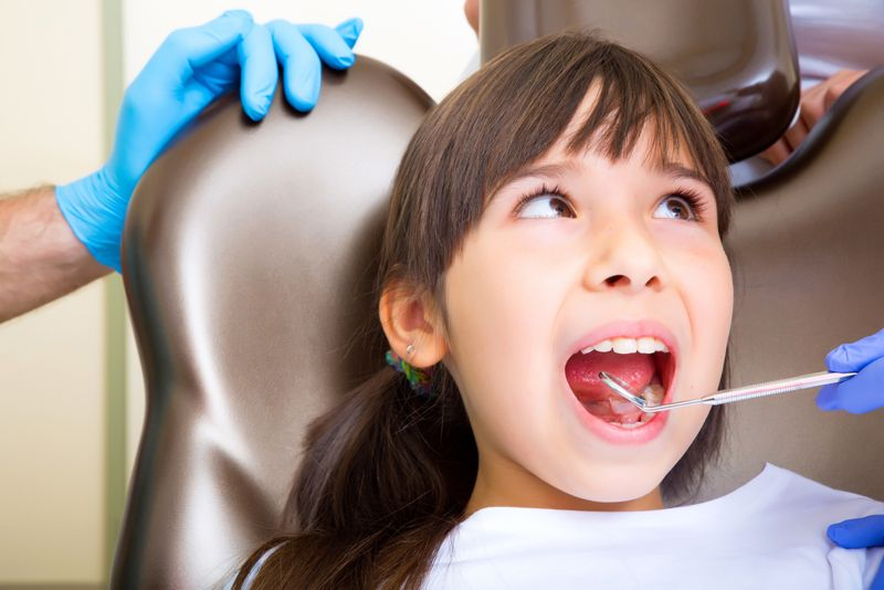 little girl at the dentist in chair