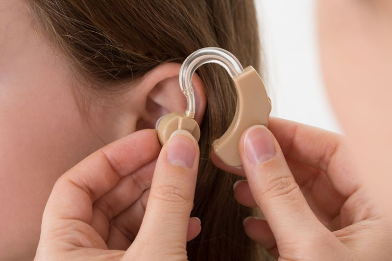 close up of audiologist inserting a hearing aid in a child's ear