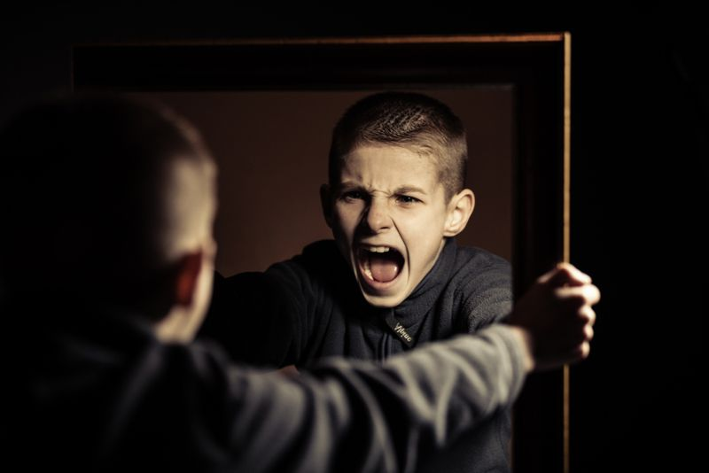 little boy yelling at himself in a mirror
