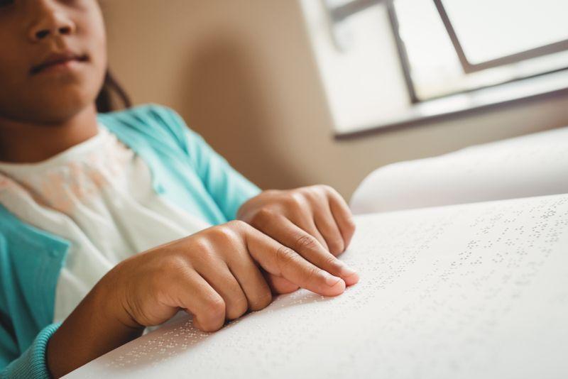 little girl reading braille