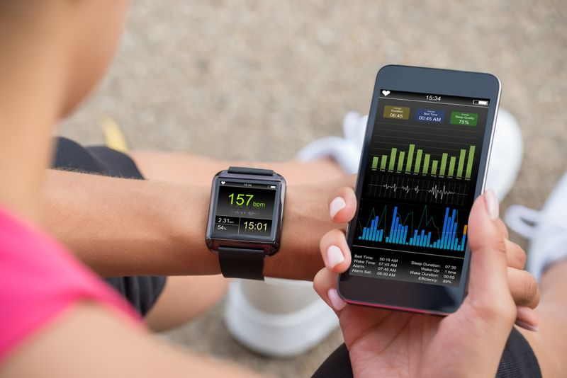woman looking at fitness tracker and app on phone