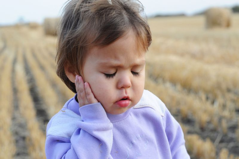 toddler girl holding her ear with pain