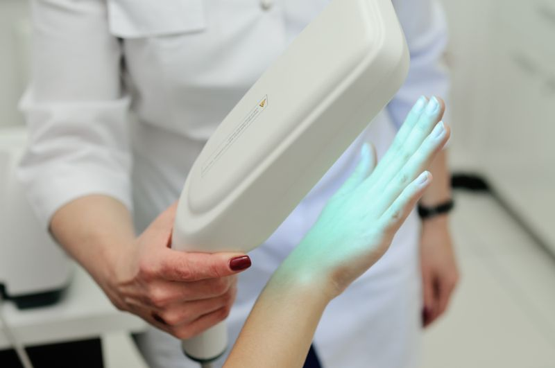 doctor holding a UV lamp over a patient's hand