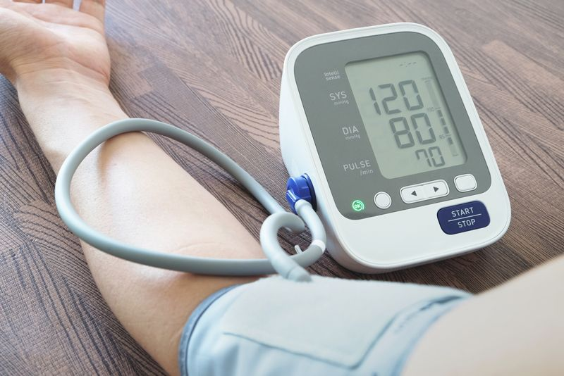 close up of blood pressure cuff and meter on person's arm