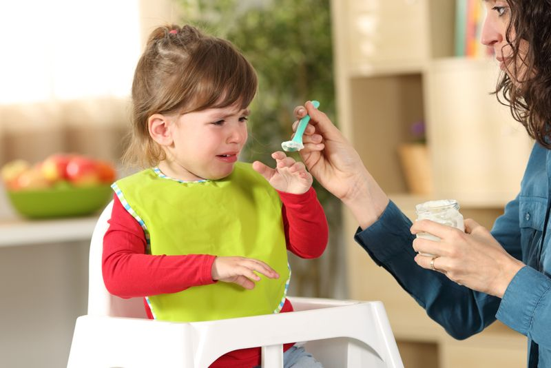 toddler girl in high chair refusing to eat