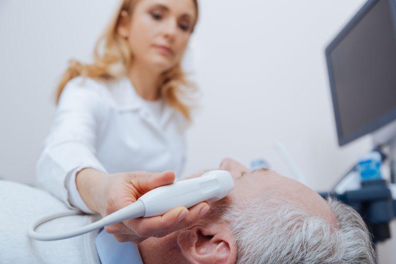 female doctor using ultrasound device on elderly patient's head