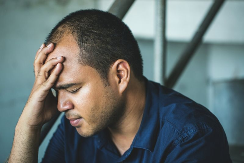 man sitting on stairs holding his head, looking sad