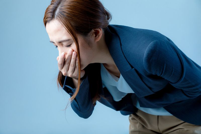 young woman feeling nauseated, hand over mouth