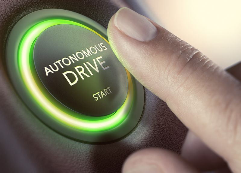 Finger pressing a push button to start a self-driving car. Composite image between a hand photography and a 3D background.