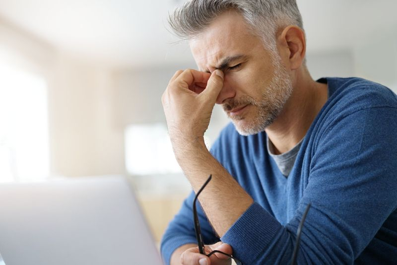 older man with headache pinching his nose