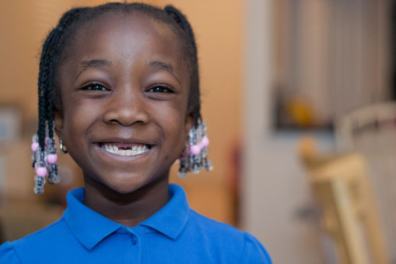 young girl with two front teeth missing
