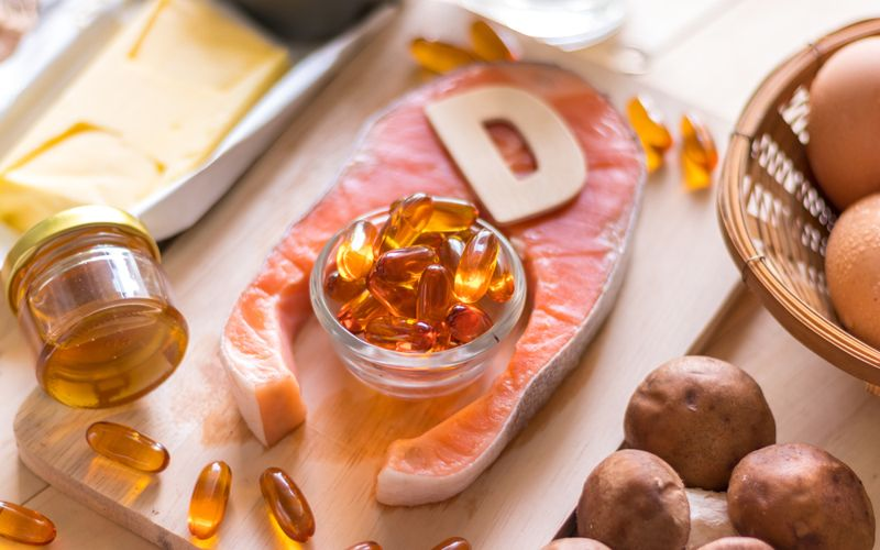 vitamin D concept with capsules, potatoes, and salmon