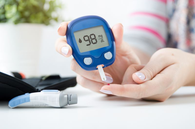 woman checking her blood sugar with a blood glucose meter