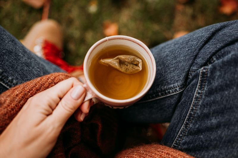 Woman drinking tea outdoors in autumn casual clothing close up of ceramic tea cup Photo taken outdoors in nature in sunlight