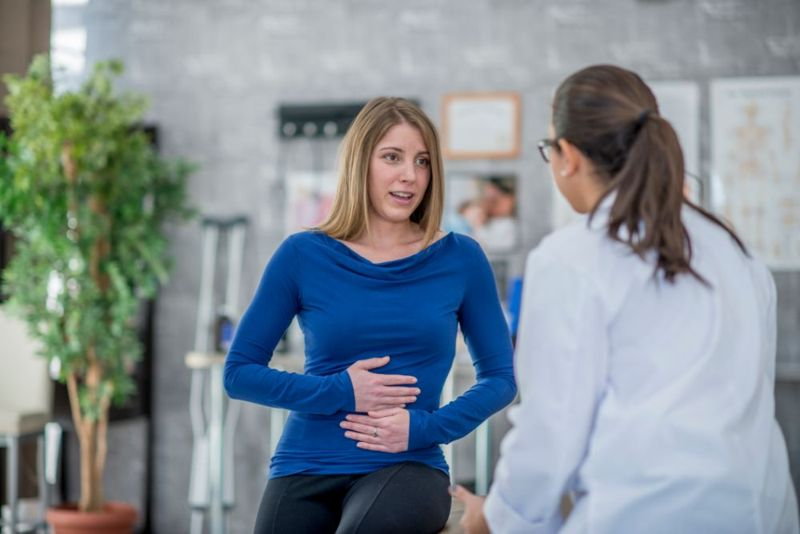 patient explaining stomach pain to female doctor