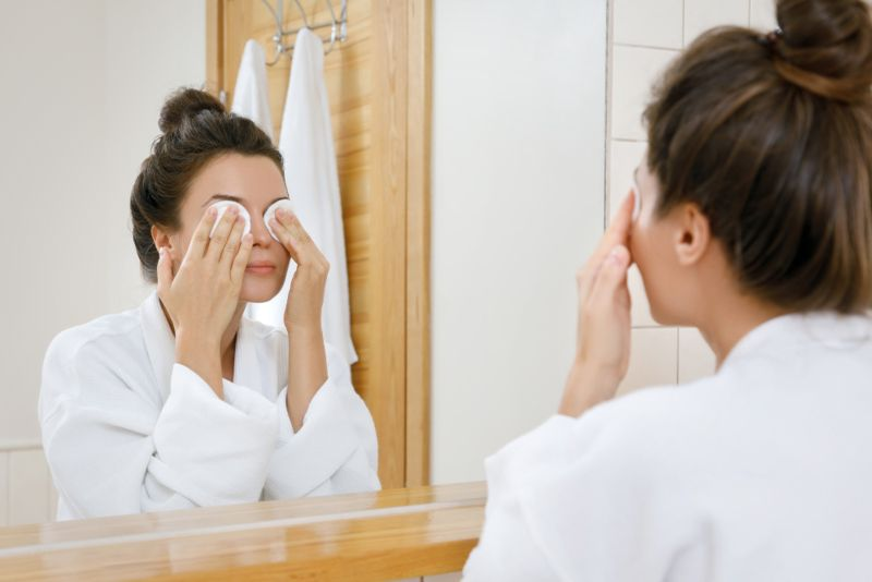 woman cleaning off her eye makeup before bed