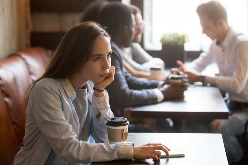 young woman alone at a coffee shop, group of people behind her