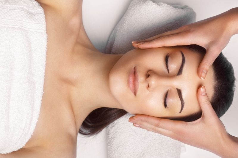 cropped image of smiling woman having temples massaged