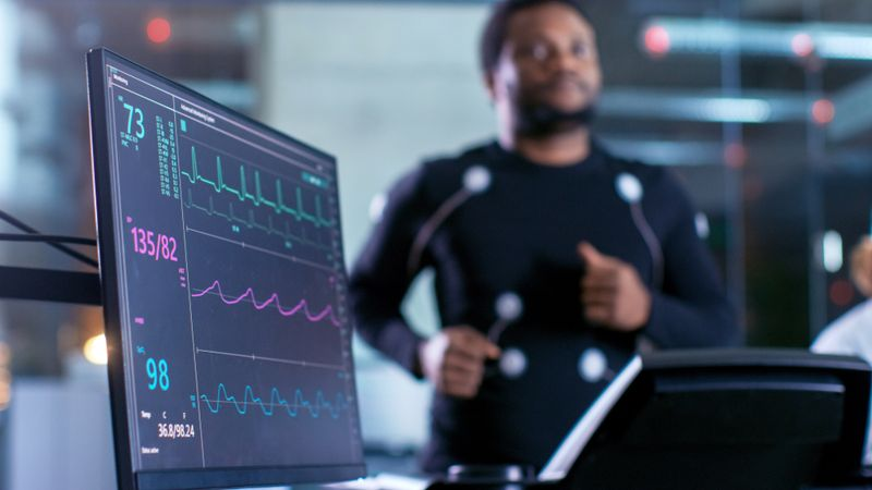 EKG screen in foreground and patient on treadmill in background