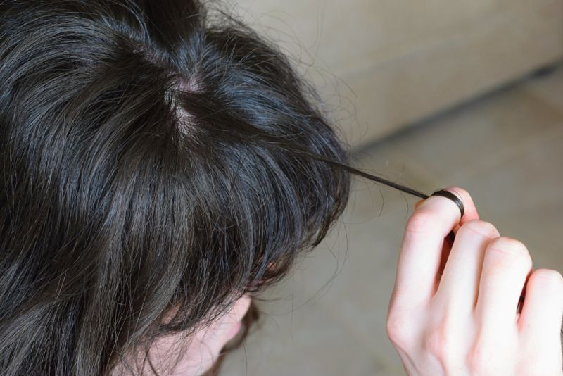 cropped image of a woman pulling on her hair