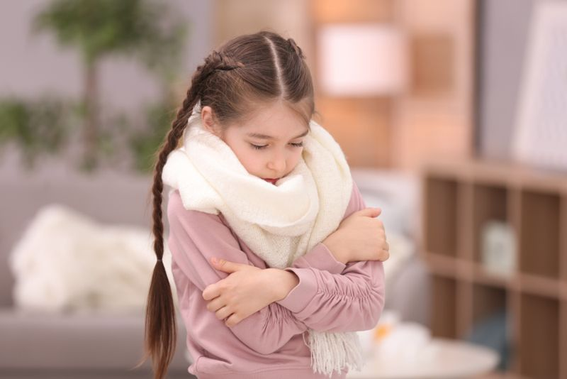 little girl wearing scarf who is cold indoors