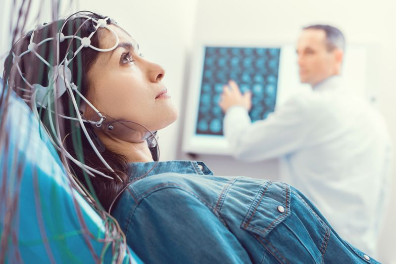 female patient getting an EEG test, doctor in background