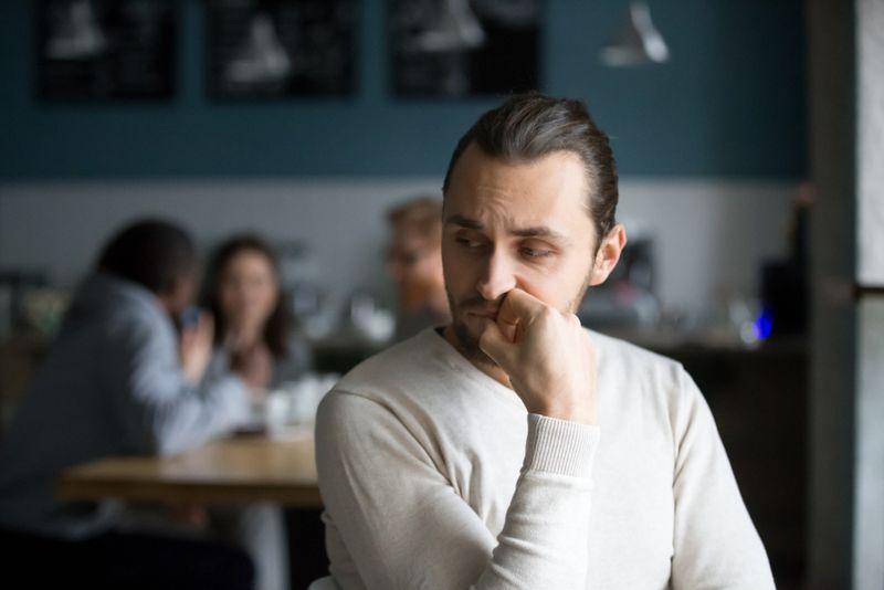 man sitting away from group of friends, alone