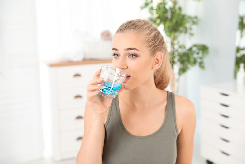 young woman using mouthwash