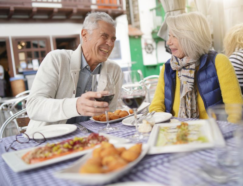 an elderly couple sharing wine and dinner