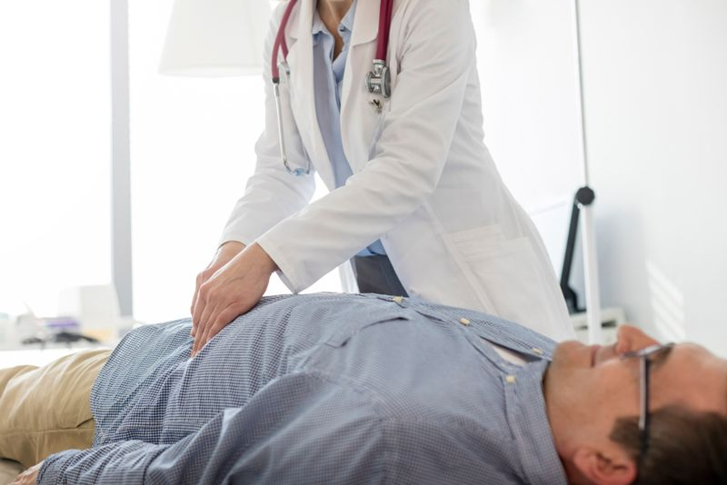 female doctor palpating middle aged male patient abdomen