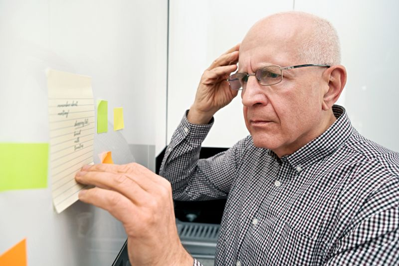 older man confused, looking at sticky notes on cupboard