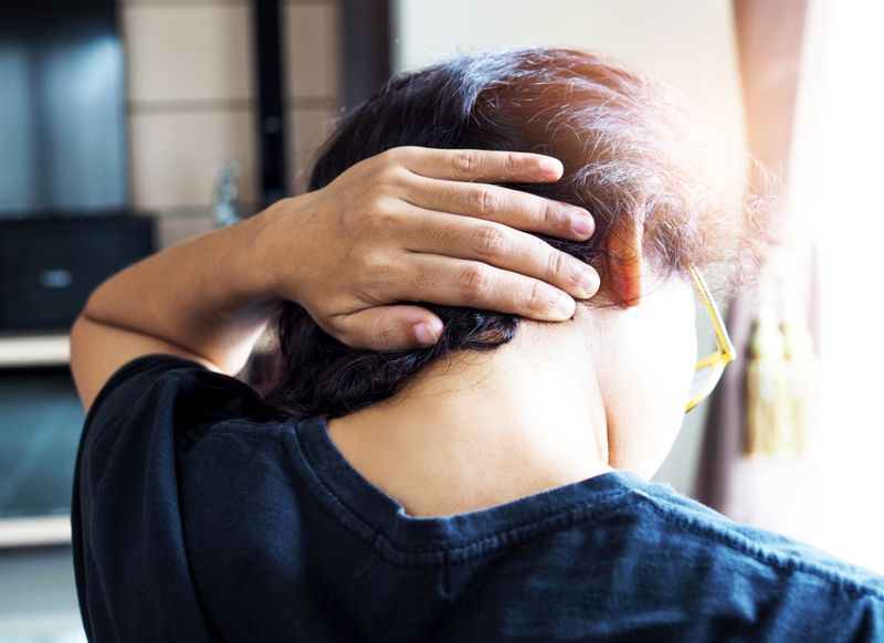 woman with occipital headache holding back of her head