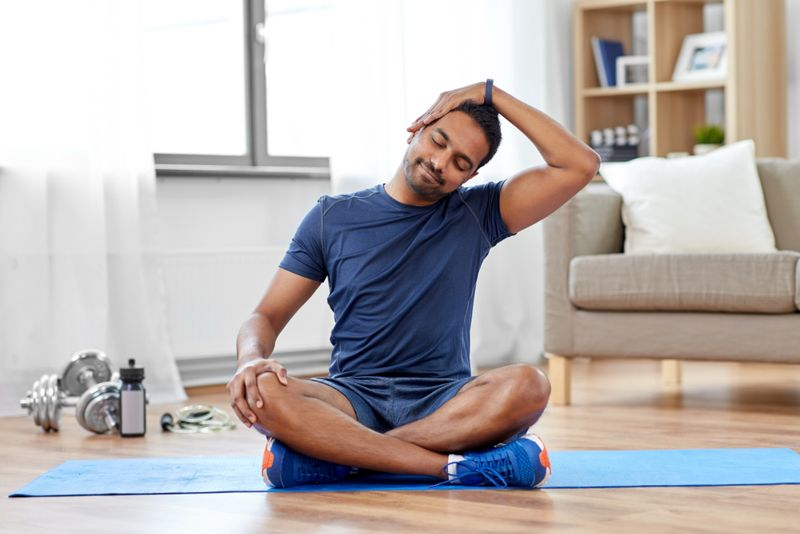 man on yoga mat doing neck stretches