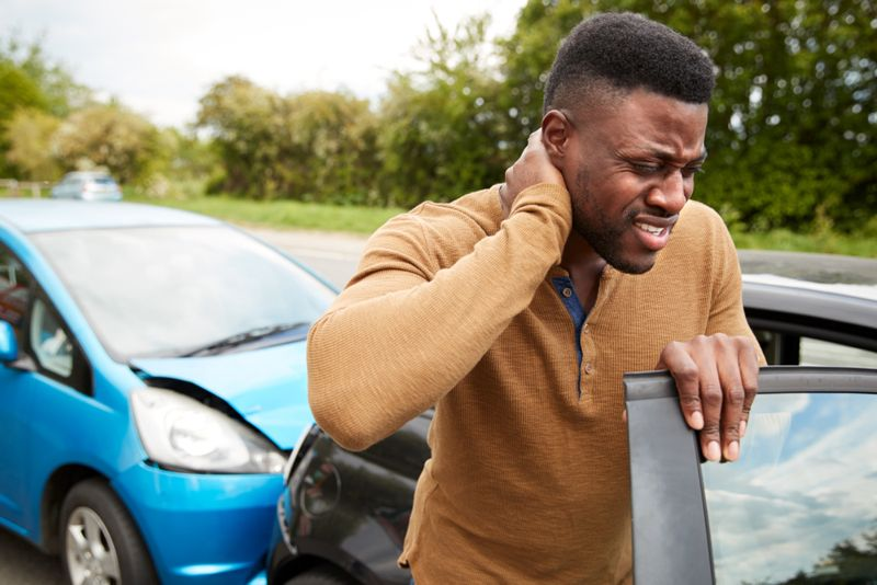 man with neck pain standing beside car that has been rear ended