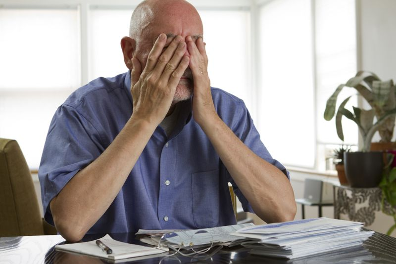 senior man at home frustrated by financial papers
