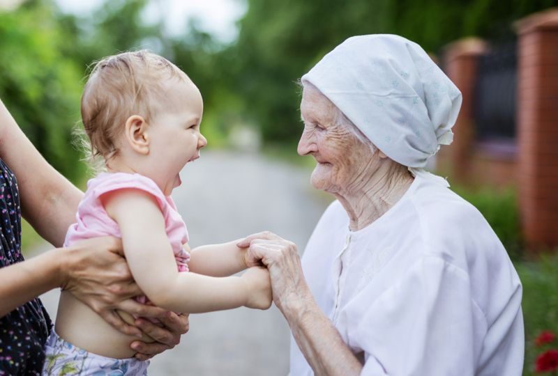 a great grandmother holding her laughing granddaughter's hands