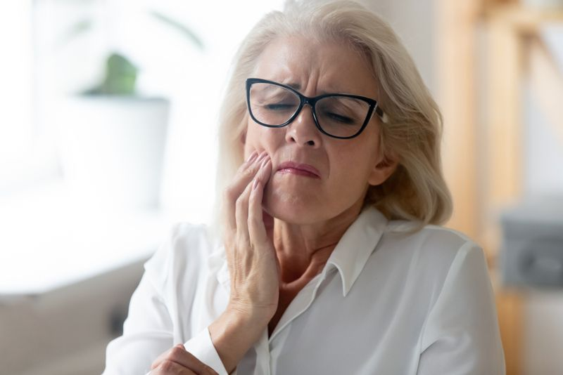 older woman with sore mouth looks in pain