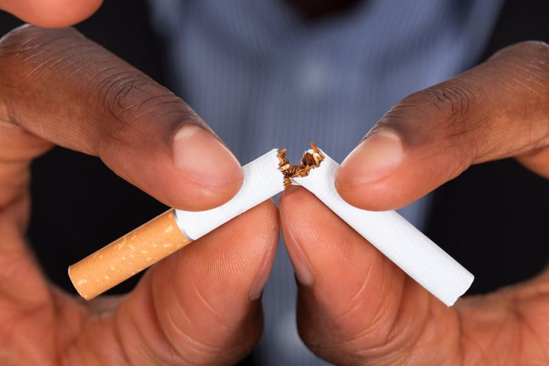 close up of hands breaking a cigarette; quit smoking concept