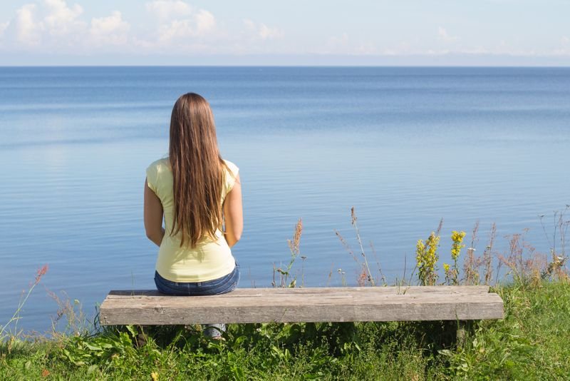 young woman sitting alone on a bench by the water