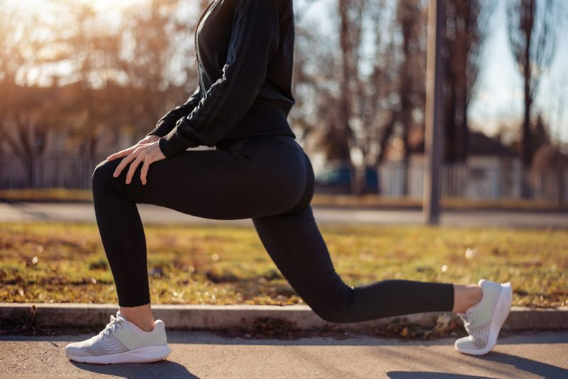 cropped image of a woman doing walking lunges outside
