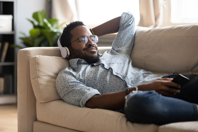 smiling man listening to music on the couch