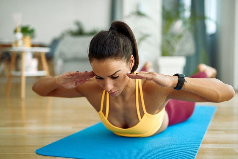young woman doing back extension superman exercise on mat