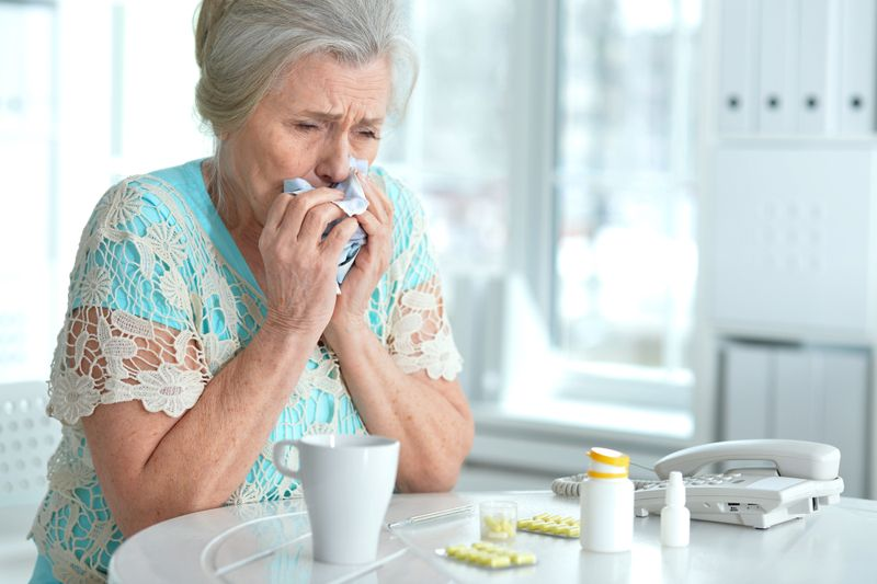 older woman surrounded by pills coughing