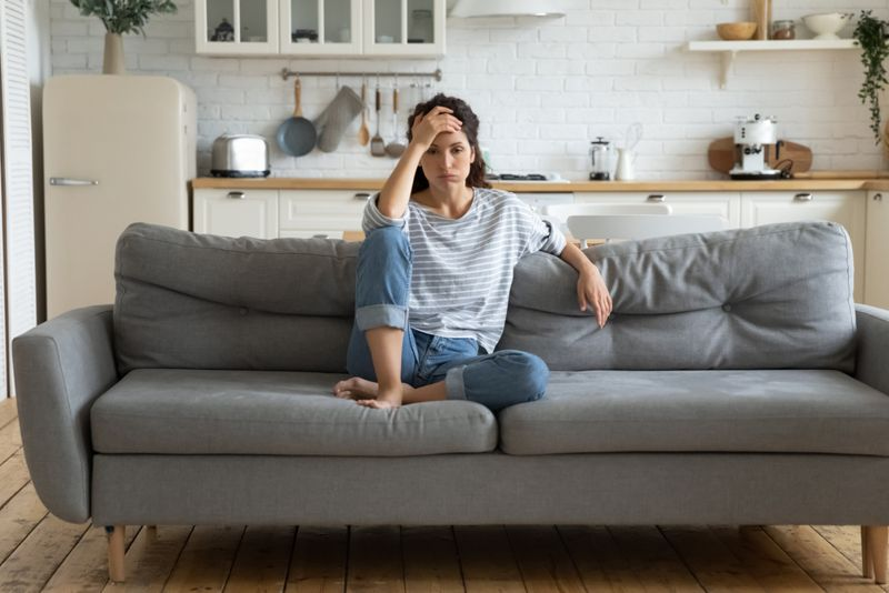 stressed, anxious, fatigued woman sitting on her couch