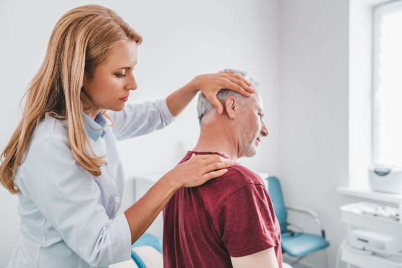 female doctor examining male patient's neck