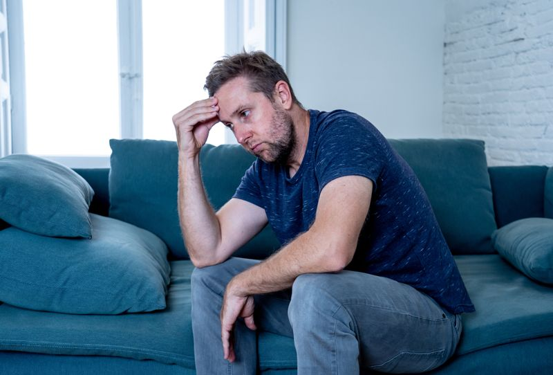 man alone in his apartment, looking unhappy