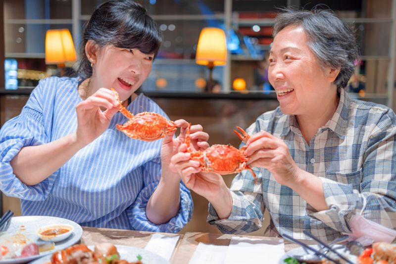 a mother and daughter sharing crab for dinner