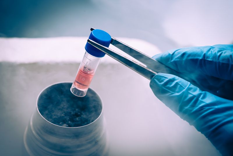 researcher using tweezers to remove vial of stem cells