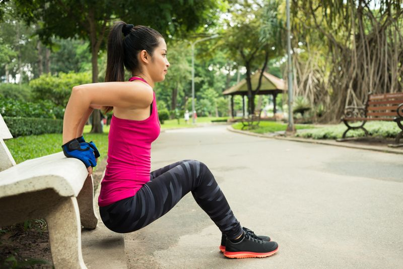 young woman doing tricep dip exercise on park bench