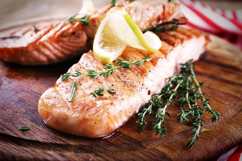 grilled salmon with lemon and thyme on a wood platter